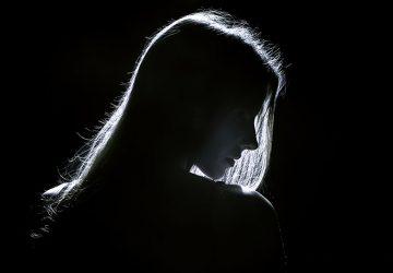silhouette d'une jeune femme triste dans l'obscurité
