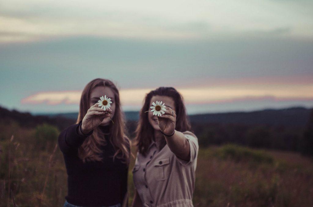 deux amis tenant une fleur à la main