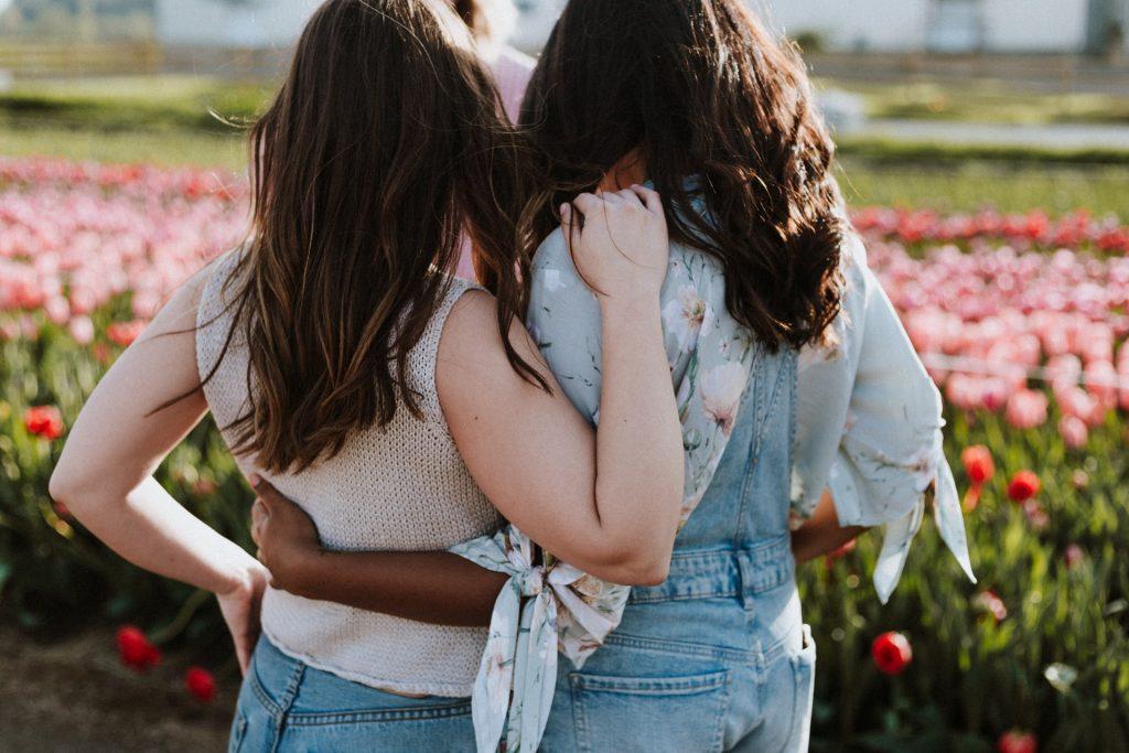 deux filles dans un champ de roses embrassant
