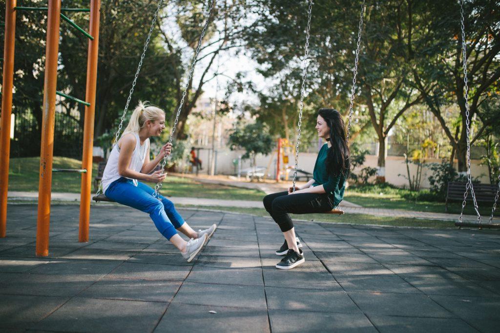 deux filles sont assises sur une balançoire