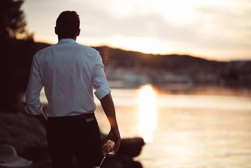 jeune homme au bord de l'eau au coucher du soleil