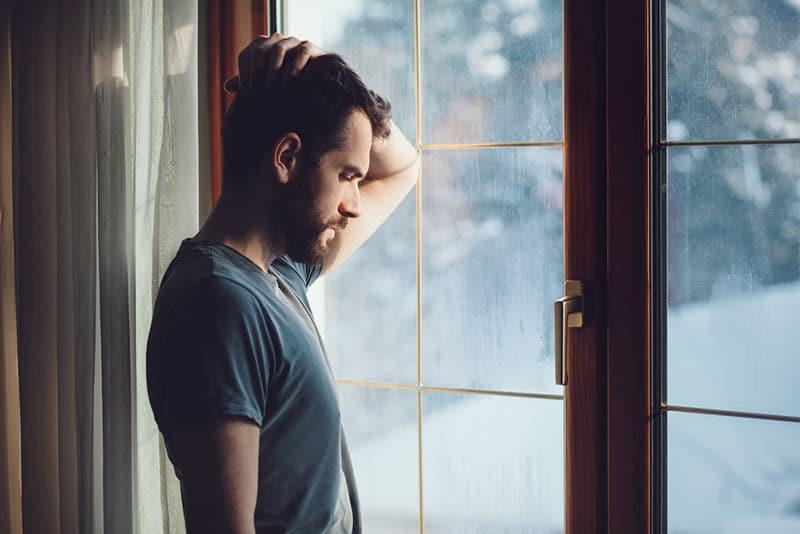 jeune homme triste près de la fenêtre
