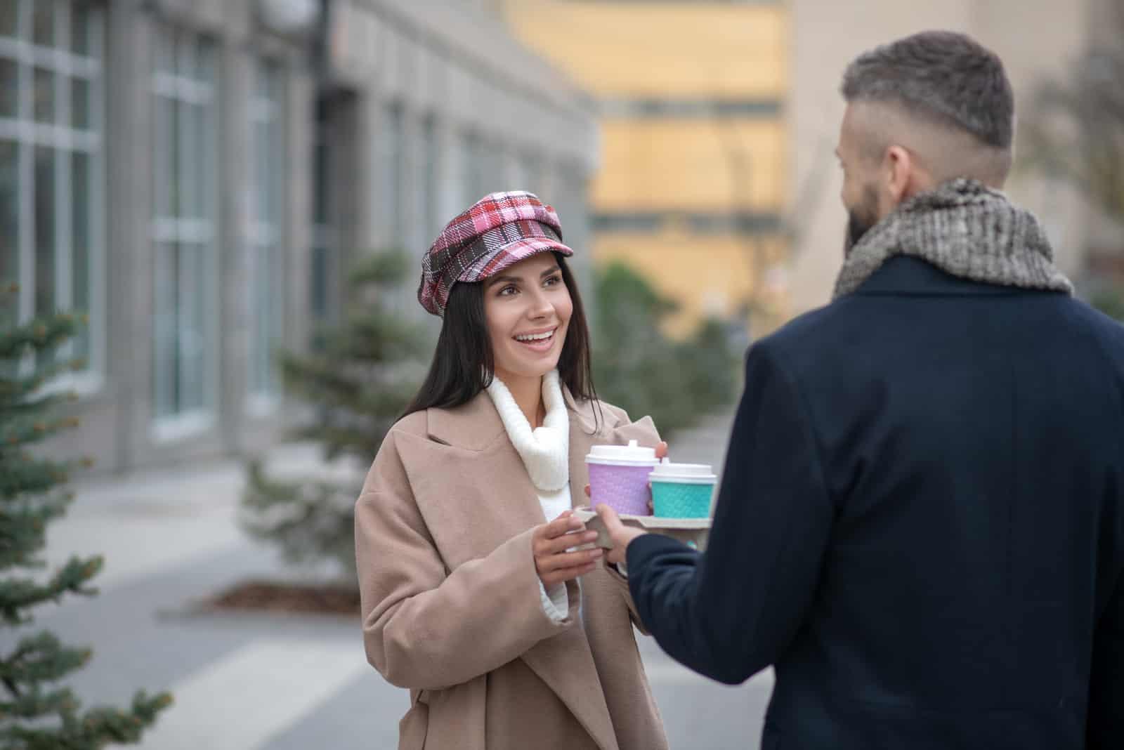 un homme debout avec une femme tenant un café à la main
