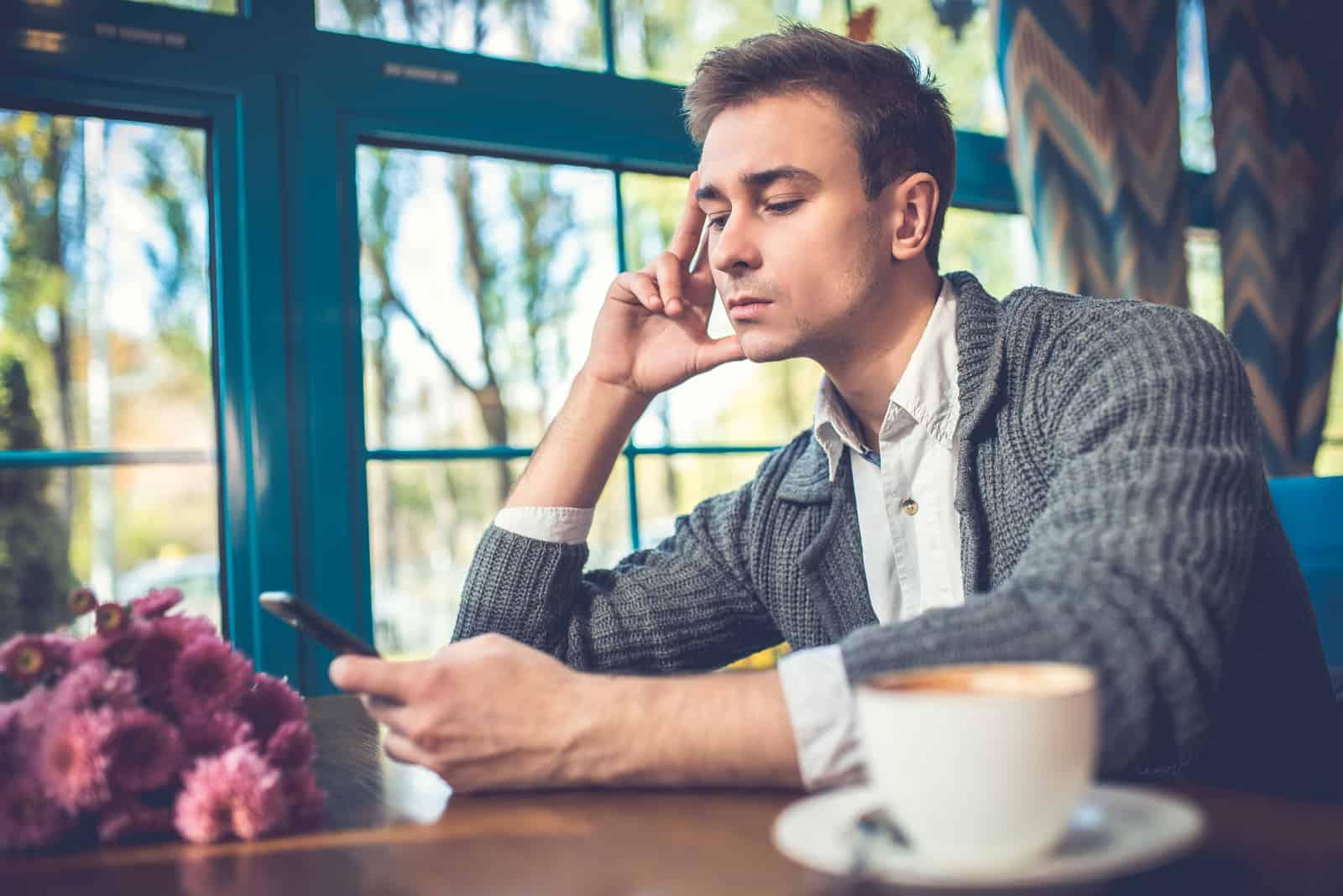 un homme est assis en train de boire du café et une clé sur le téléphone