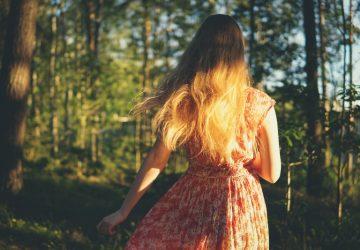 une femme en robe se promène dans les bois