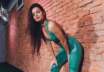 une femme dans un T-shirt vert appuyé contre un mur