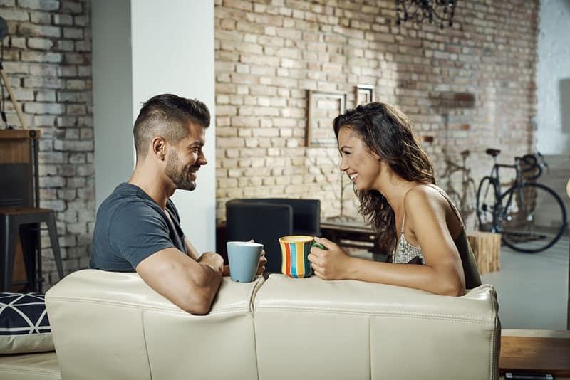 heureux jeune couple, boire du café et parler