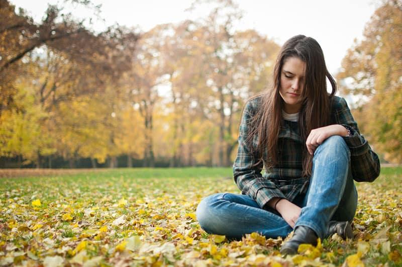 triste jeune femme assise sur l'herbe dans le parc