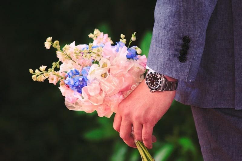 un homme en costume porte des fleurs