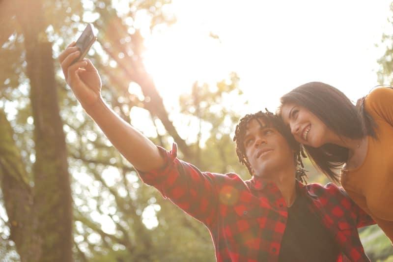 un homme et une femme prennent des photos