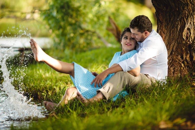 un homme et une femme sont assis au bord de la rivière