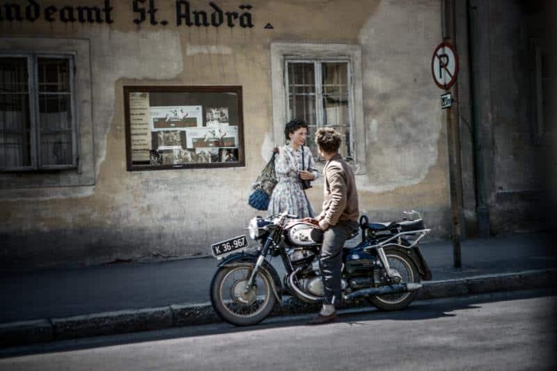un homme sur une moto parler à une femme