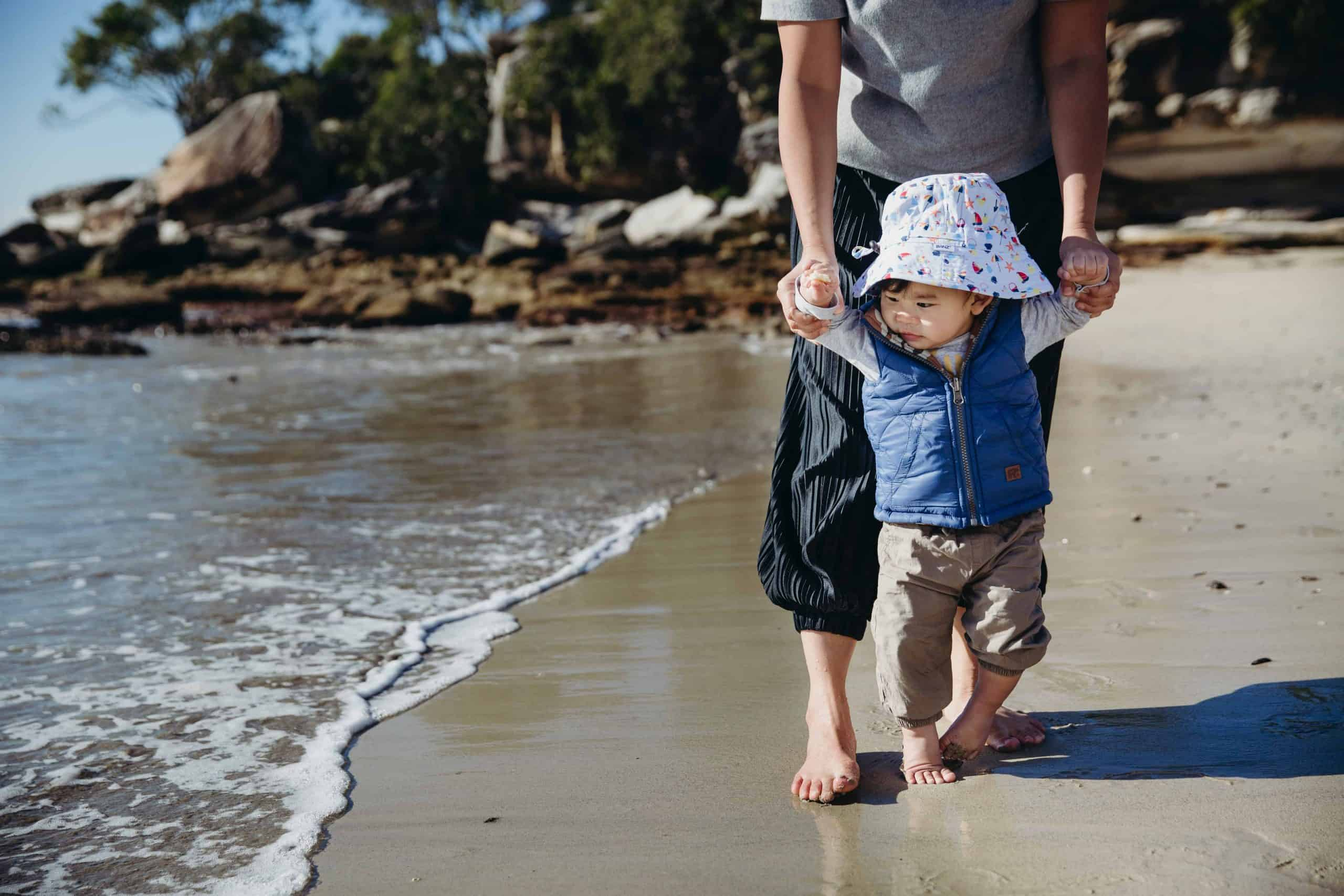 une femme promène un enfant sur la plage