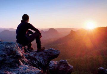 un homme assis sur un rocher