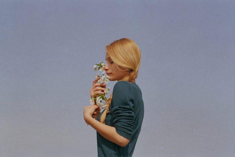 une femme se tient avec un bouquet de roses à la main
