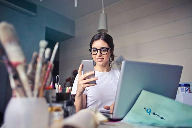 jeune femme, téléphone, par, elle, ordinateur portable