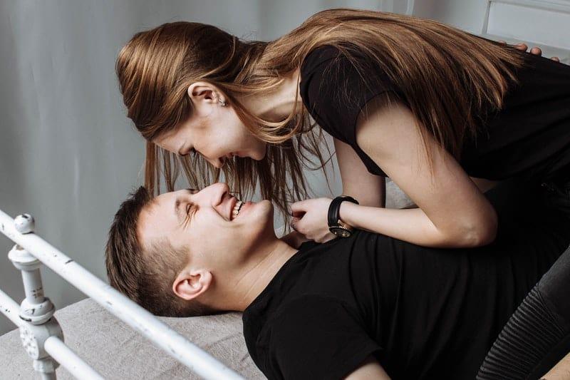 un homme et une femme riant au lit