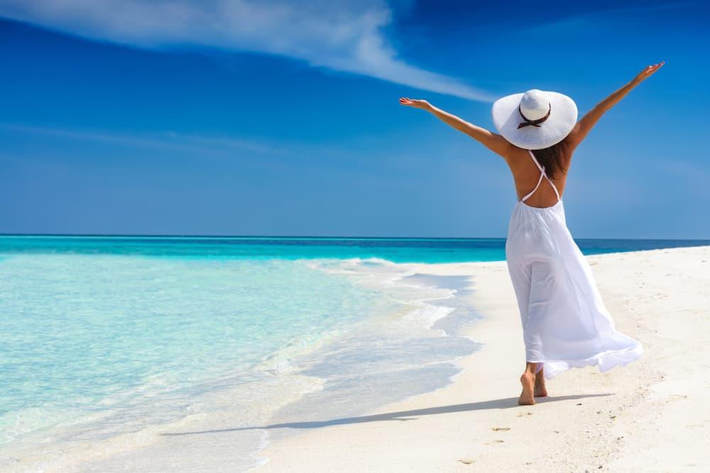 une femme aux bras tendus définit la plage