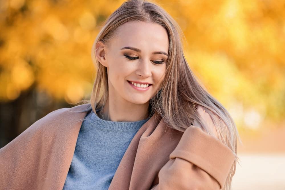 une femme aux cheveux blonds regarde le sol