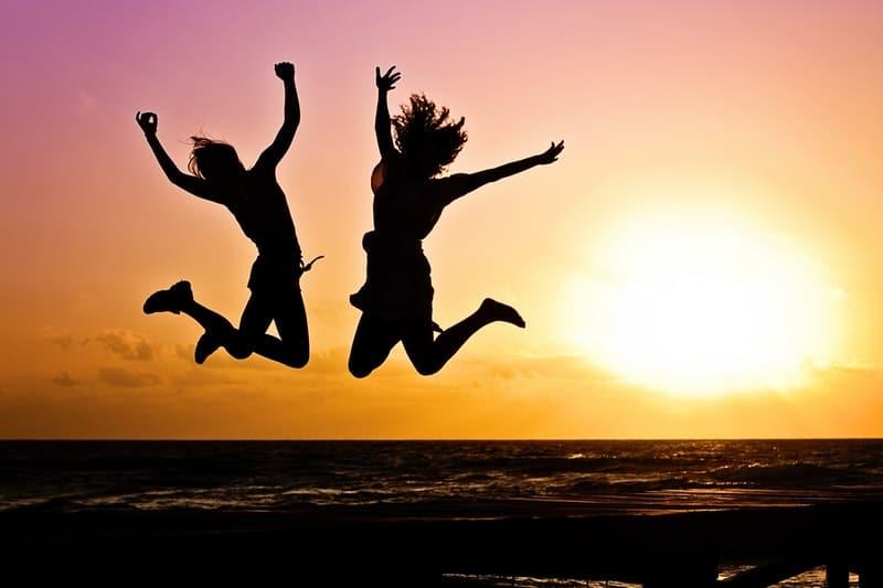 deux femmes sautent en l'air au coucher du soleil