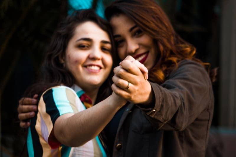 filles souriantes, main dans la main
