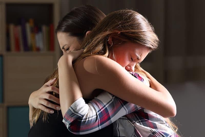 jeunes amies pleurer et étreindre