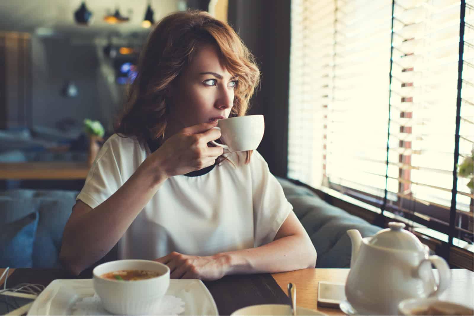 femme assise seule dans un café buvant du café
