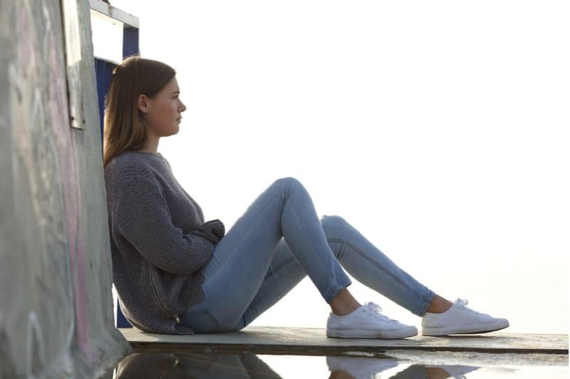 femme triste assise sur le toit