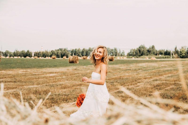 Une femme souriante dans un champ brun