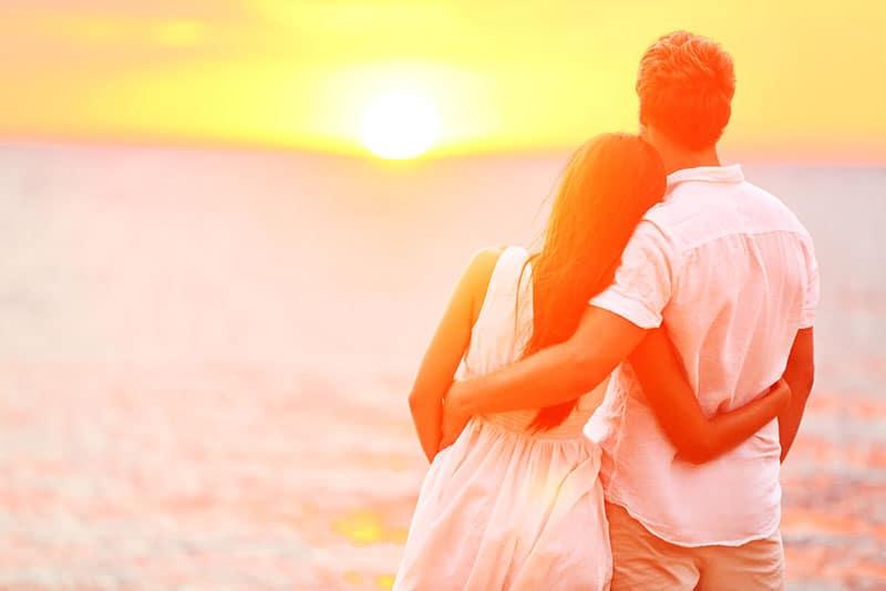 jeune couple, apprécier, les, coucher soleil, sur, plage