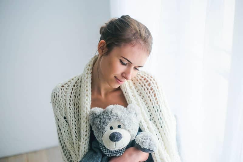 jeune femme avec un ours dans ses mains