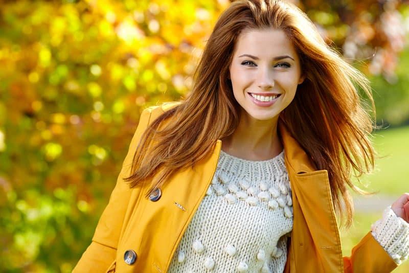 jeune femme en manteau rouge dans la nature