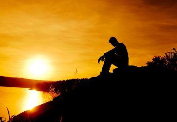 homme triste assis au bord de l'eau au coucher du soleil
