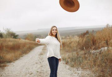une femme aux cheveux blonds jette un chapeau