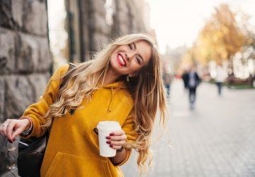 une femme blonde avec du café à la main