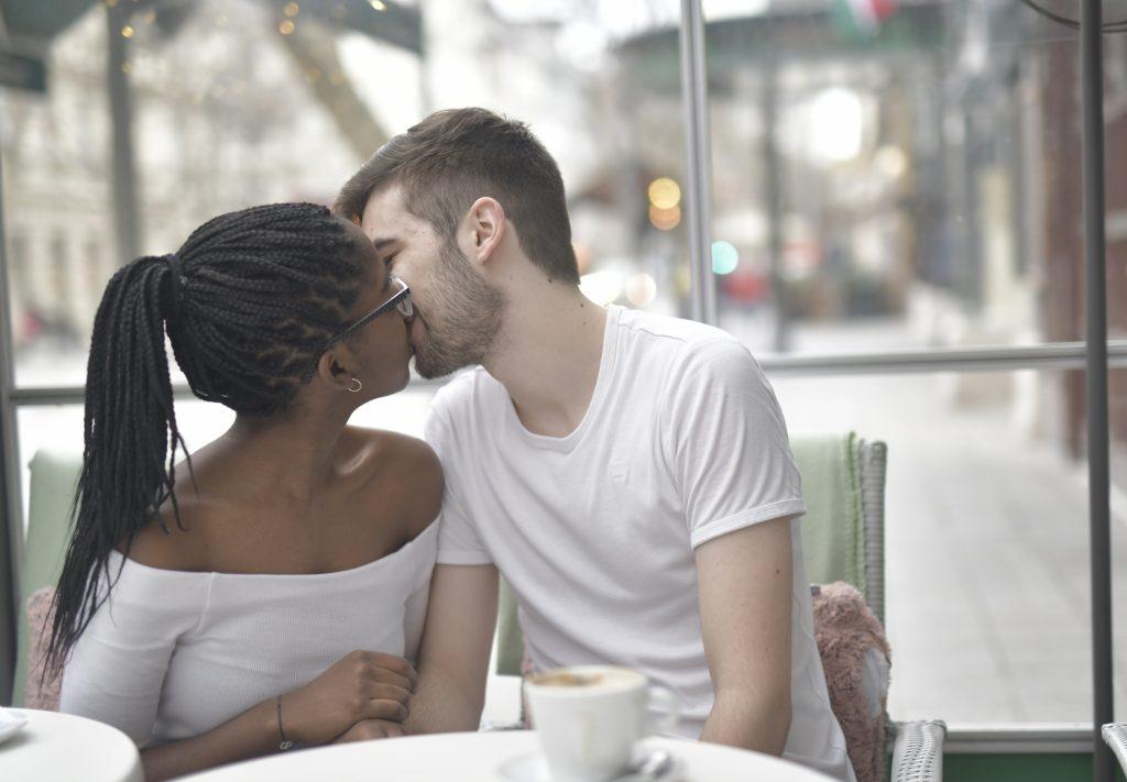 un homme et une femme s'asseoir et s'embrasser