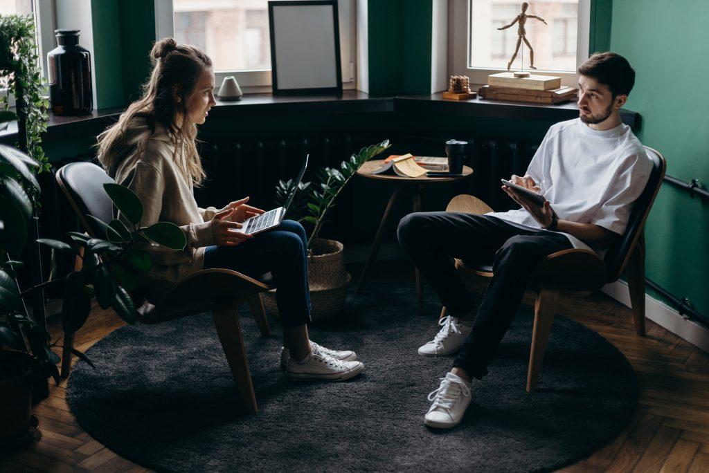 un homme et une femme sont assis avec un ordinateur à la main