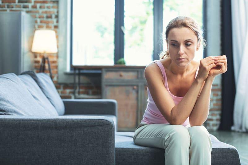femme blonde mature déprimée sur canapé