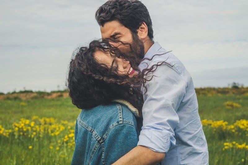 un homme avec une barbe embrasse une femme satisfaite