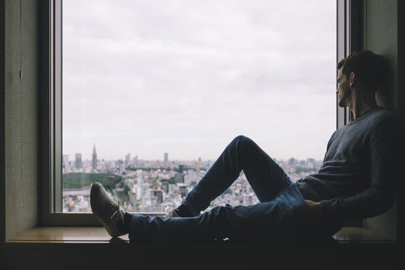 un homme est assis près de la fenêtre