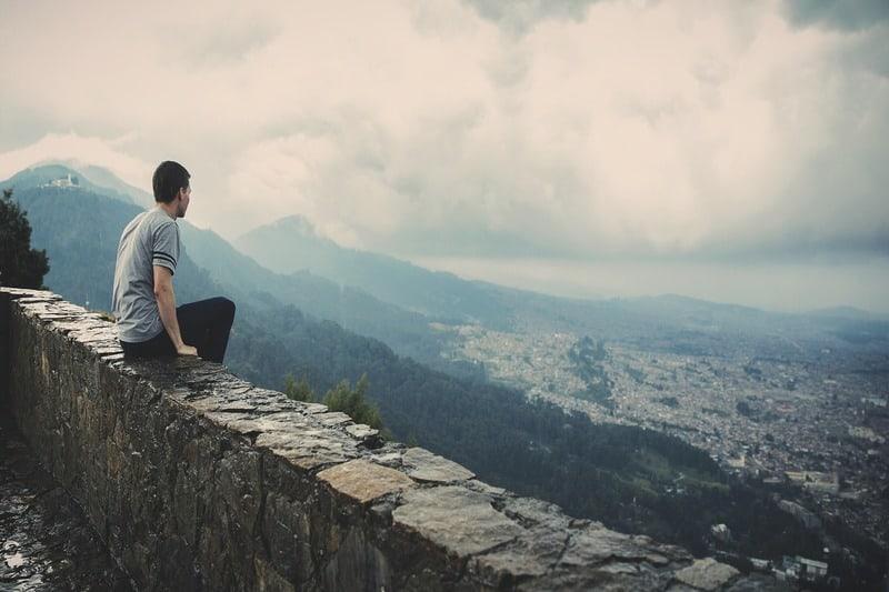 un homme est assis sur un mur au-dessus de la ville