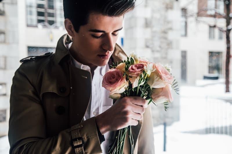 un homme tenant un bouquet de fleurs