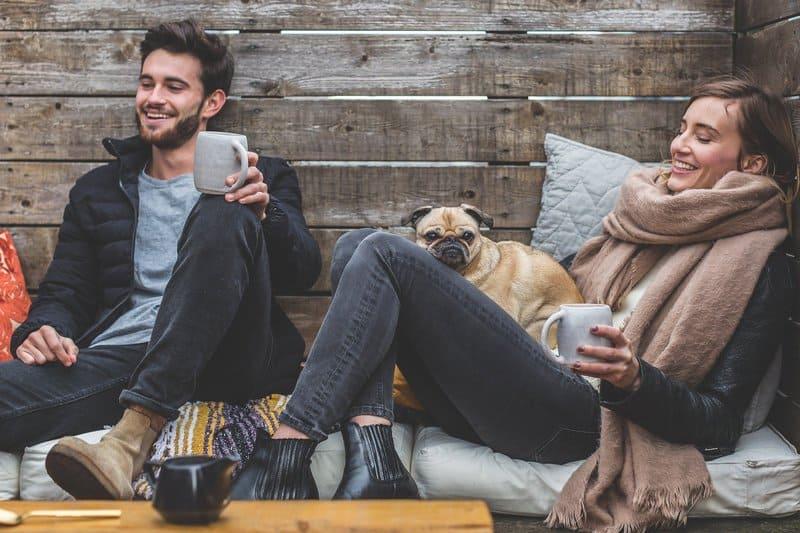 une femme et un homme sont assis avec un chien sur un matelas