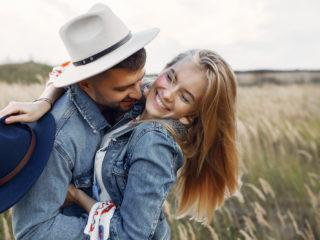un homme et une femme s'embrassent debout dans un champ