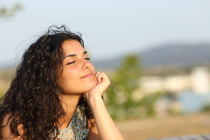 heureuse jeune femme appréciant le soleil