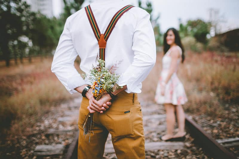 homme sur le point de surprendre sa petite amie avec des fleurs