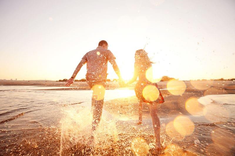 jeune couple, courant, sur, plage, dans, coucher soleil