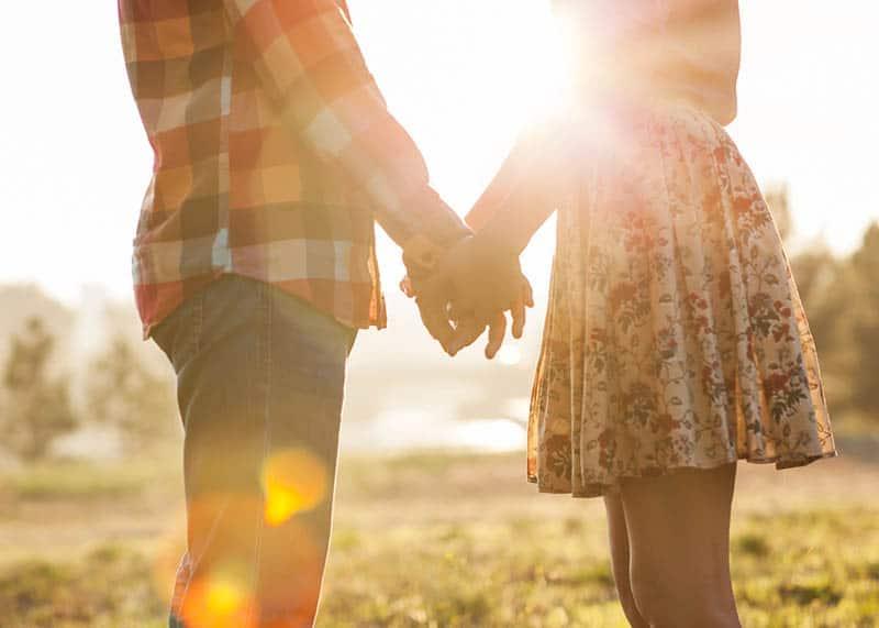 jeune couple, tenant mains, dans soleil