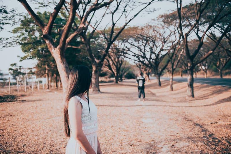 jeune couple triste dans le parc au coucher du soleil