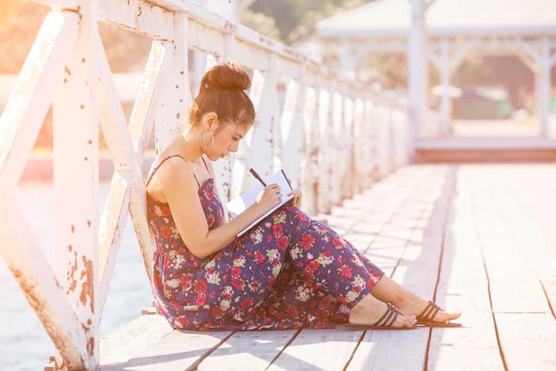 jeune femme écrivant une lettre sur un quai
